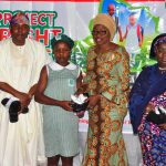R-L: Deputy Governor of Lagos State, Dr. (Mrs.) Oluranti Adebule and Wife of the Governor, Mrs. Bolanle Ambode, presenting shoes and socks to pupils of State Primary Schools in Lagos during the launching of Project Bright Steps, a Children Empowerment Project by Wife of the Governor & Founder of HOFOWEM at the Event Centre, Agidingbi, Ikeja. With them are Chairman, House Committee on Education, Hon. Olarenwaju Ogunyemi and Head of Service, Mrs. Olabowale Ademola